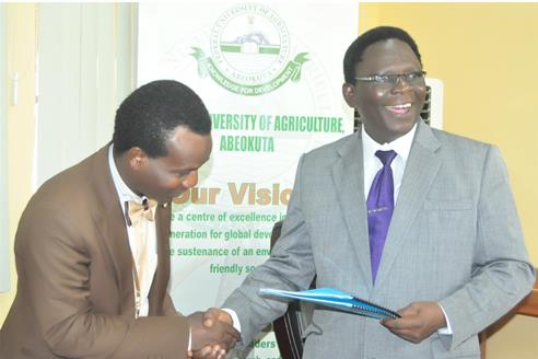 The Vice-Chancellor, Prof. Olusola Oyewole (Right), presenting copies of the MoU to the representative of Arewa Cotton, Mr. Bayo Olayemi.